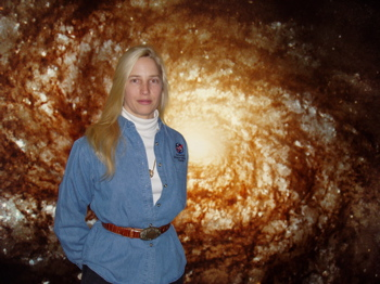 Darlene Kellner in front of Hubble Space Telescope Spiral Galaxy Picture